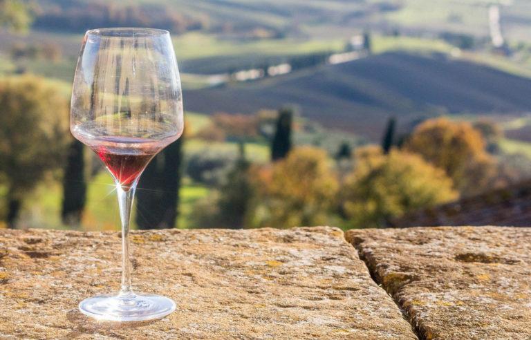 Glas Rotwein auf Mauer